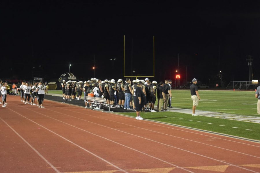 The football team watches silently as the players on the field face off against the Falcons. This game ended with the Yellow Jackets claiming another win.