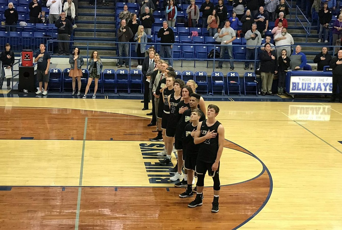 The varsity team stands for the national anthem before their game again Marshfield on December 4th.