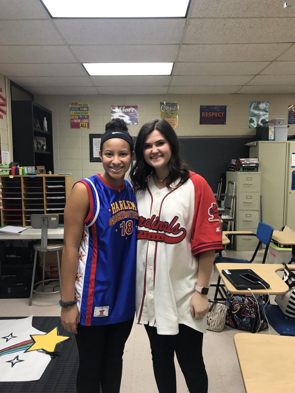 Seniors Bailey Riggs and Tori Lefler wearing a cardinals and a Harlem Globetrottes jerseys.
