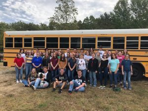 The Psychology classes standing in front of the bus at the College, accompanied by the Colleges dog Sam.