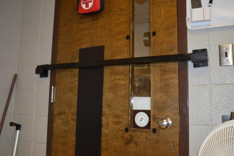 The safety bar is put across the door inserted into slots that hold the bar in place so intruders cannot get into the classroom to harm the students. The LTCC and the high school have two different setups. The LTCC has the bar that is shown in the picture and the high school has a small red locking device that goes into a slot at the bottom of the door.